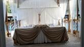 Официална маса и стена зад младоженци
