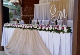 Официална маса и стена зад младоженците